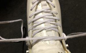 スケート靴の紐を引っ張っている